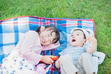 レジャーシートの上に寝転ぶ姉弟の写真素材 [FYI01955228]