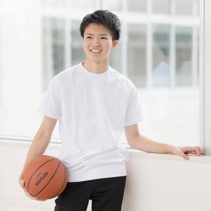 廊下でバスケットボールを持ち微笑む男子学生の写真素材 [FYI01955241]