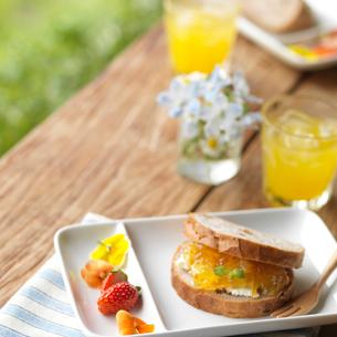 野花を飾ったジャムのサンドイッチとイチゴの写真素材 [FYI01955290]