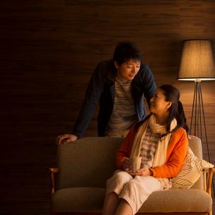 ソファーに座り談笑をするミドル夫婦の写真素材 [FYI01955316]