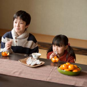 こたつで干し芋とみかんを食べる兄妹の写真素材 [FYI01955328]