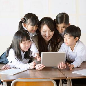 タブレットPCを見る小学生と先生の写真素材 [FYI01955376]