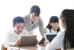 先生にプログラミングの勉強を教わる小学生  ARの写真素材 [FYI01955388]
