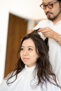 美容師にヘアセットをしてもらう女性の写真素材 [FYI01955462]