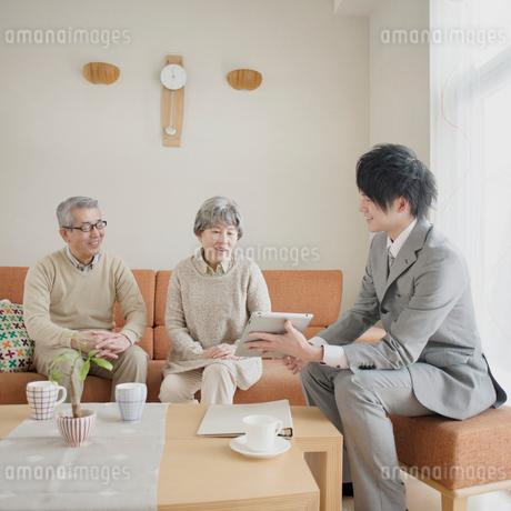 ビジネスマンの説明を聞くシニア夫婦の写真素材 [FYI01955473]