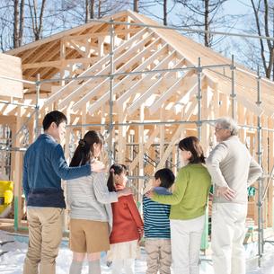 建設途中の家の前で談笑をする3世代家族の後姿の写真素材 [FYI01955507]