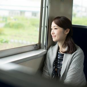 電車に乗り景色を眺める女性の写真素材 [FYI01955515]