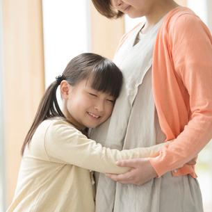 母親のお腹に耳をあてる女の子の写真素材 [FYI01955540]