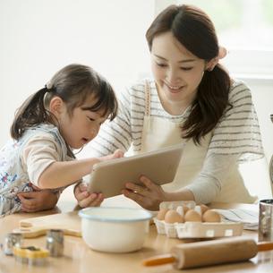 タブレットPCでレシピを調べる親子の写真素材 [FYI01955544]