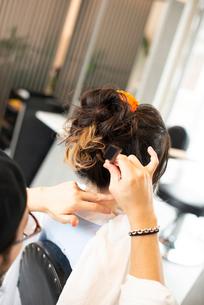 美容師にヘアセットをしてもらう女性の後姿の写真素材 [FYI01955624]