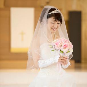 教会でブーケを持ち微笑む花嫁の写真素材 [FYI01955627]