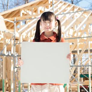 建設途中の家の前でメッセージボードを持ち微笑む女の子の写真素材 [FYI01955644]