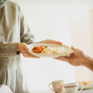 料理を手渡すカップルの手元の写真素材 [FYI01955658]