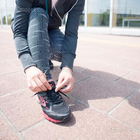 靴紐を結び直す女性の足元の写真素材 [FYI01955683]