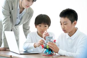先生にプログラミングの勉強を教わる小学生の写真素材 [FYI01955735]