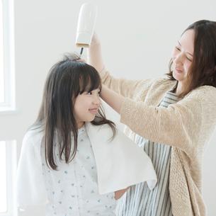 母親に髪を乾かしてもらう女の子の写真素材 [FYI01955824]