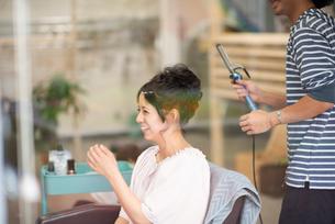 美容師にヘアセットをしてもらう女性の写真素材 [FYI01955885]