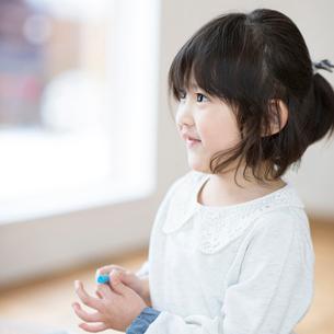 クレヨンを持ち微笑む女の子の写真素材 [FYI01955904]