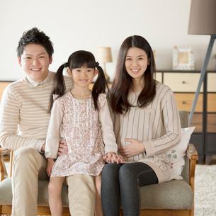 ソファーに座り微笑む家族の写真素材 [FYI01955907]