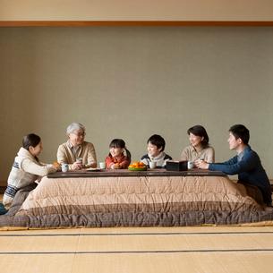 こたつで談笑をする3世代家族の写真素材 [FYI01955995]