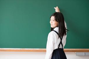 黒板の前でチョークを持つ小学生の写真素材 [FYI01956002]