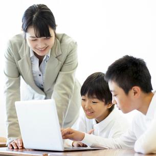 先生にプログラミングの勉強を教わる小学生の写真素材 [FYI01956030]