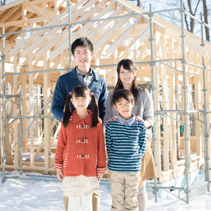 建設途中の家の前で微笑む家族の写真素材 [FYI01956041]