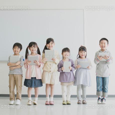 タブレットPCを持ち微笑む小学生の写真素材 [FYI01956081]