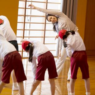 体育館で準備運動をする小学生と先生の写真素材 [FYI01956095]