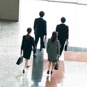オフィスのロビーを歩くビジネスマンとビジネスウーマンの後姿の写真素材 [FYI01956138]