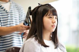 美容師にヘアセットをしてもらう女性の写真素材 [FYI01956240]