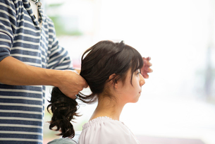 美容師にヘアセットをしてもらう女性の写真素材 [FYI01956250]