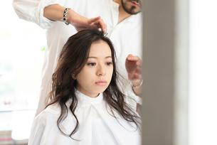 美容師にヘアセットをしてもらう女性の写真素材 [FYI01956320]