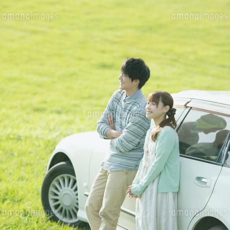 車に寄りかかり微笑むカップルの写真素材 [FYI01956381]