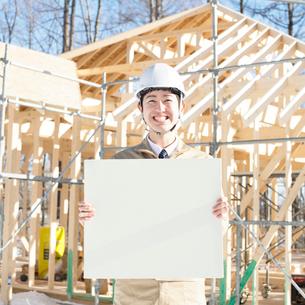 建設途中の家の前でメッセージボードを持ち微笑む作業員の写真素材 [FYI01956395]