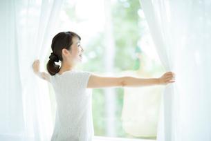 カーテンを開ける女性の写真素材 [FYI01956413]