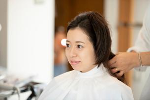 美容師にヘアセットをしてもらう女性の写真素材 [FYI01956441]