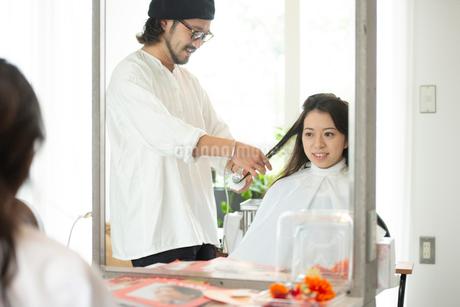 美容師にヘアセットをしてもらう女性の写真素材 [FYI01956478]