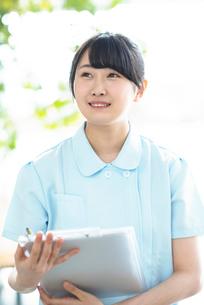 カルテを持ち微笑む看護師の写真素材 [FYI01956536]