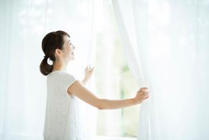 カーテンを開ける女性の写真素材 [FYI01956543]