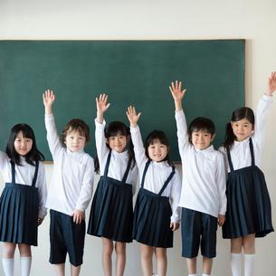 黒板の前に並び手を挙げる小学生の写真素材 [FYI01956624]