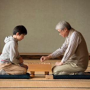 和室で将棋をする祖父と孫の写真素材 [FYI01956763]