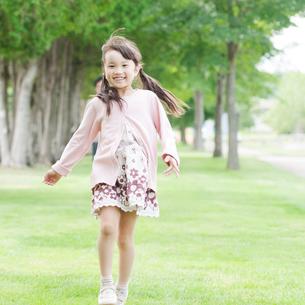公園でスキップをする女の子の写真素材 [FYI01956778]