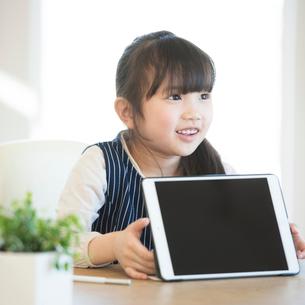 タブレットPCを持ち微笑む女の子の写真素材 [FYI01956792]