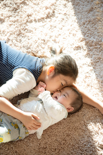 カーペットの上に寝転ぶ姉妹の写真素材 [FYI01956810]