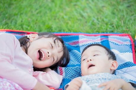 レジャーシートの上に寝転ぶ姉弟の写真素材 [FYI01956860]