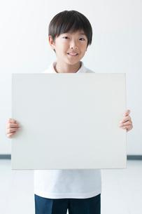 ホワイトボードを持ち微笑む小学生の写真素材 [FYI01956890]