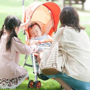 ベビーカーで眠る赤ちゃんを見守る母親と女の子の写真素材 [FYI01956893]