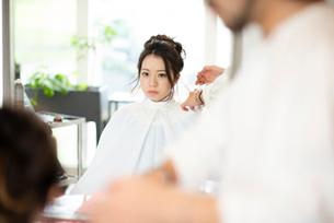 美容師にヘアセットをしてもらう女性の写真素材 [FYI01956916]
