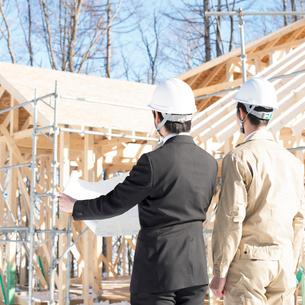 建設途中の家の前で打ち合わせをするビジネスマンと作業員の後姿の写真素材 [FYI01956948]